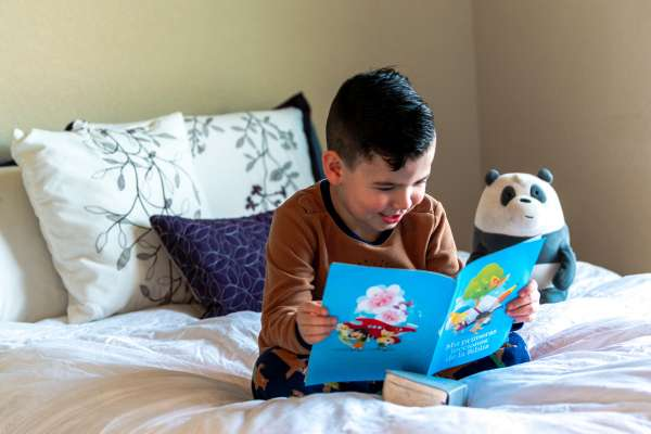 Young boy sitting on bed reading a book